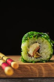 Суши на деревянной доске. роллы с рыбой на темном фоне.
