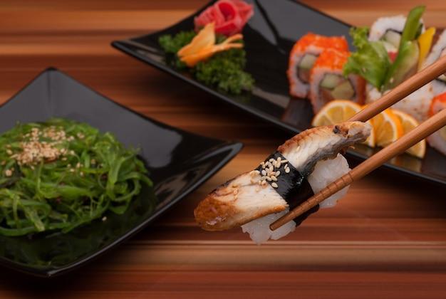 Суши на палочках для еды крупным планом на фоне суши-блюд