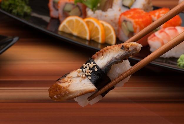 젓가락 위의 스시는 스시 요리의 배경에 닫혀 있다
