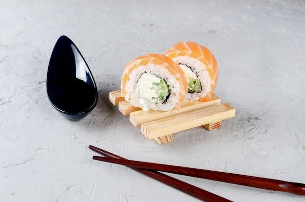 Суши филадельфия на деревянной тарелке, соевый соус и палочки для еды