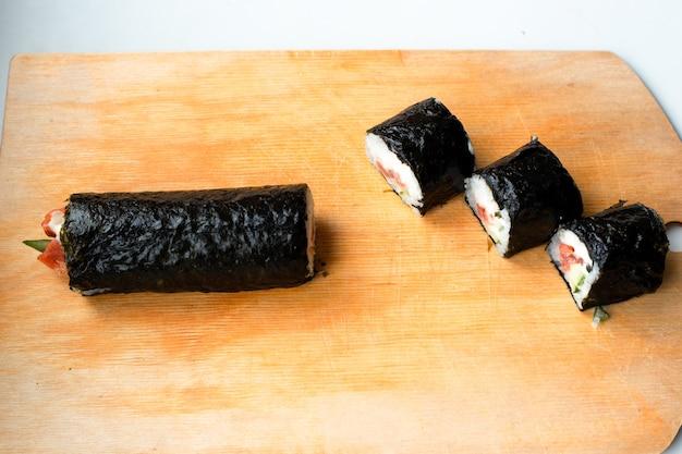 Кусочки суши на деревянной приготовленной разделочной доске дома