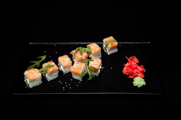 黒の背景で区切られた箸の間に置かれた寿司の部分。人気の寿司料理。非常に高解像度の画像。