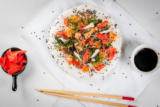 Sushi pizza with salmon, hayashi wakame, daikon, pickled ginger, red caviar.