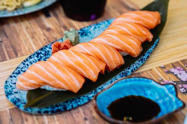 Суши-тарелка из нигири из лосося с соевым соусом на террасе