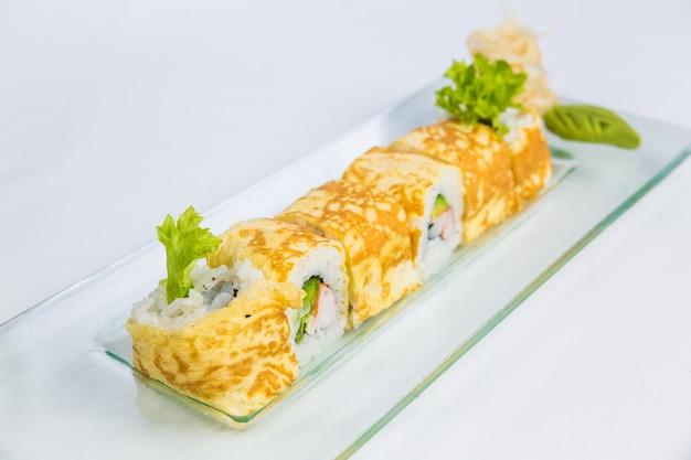 白い壁に寿司プレート。アジアの食品配達の概念