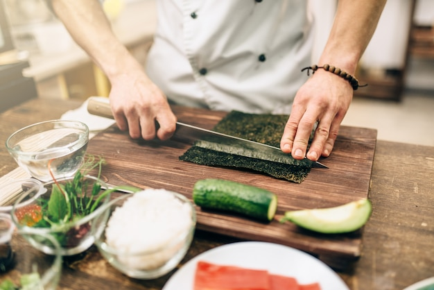 Приготовление суши, традиционные японские блюда. мужчина повар делает роллы на кухне