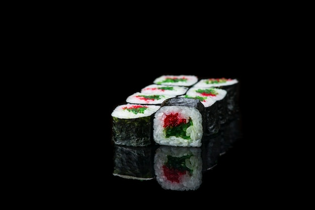 Sushi roll on a black background reflection  japanese food close up