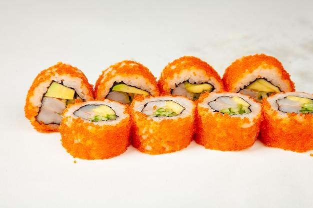 Суши-ролл калифорния ролл на белом фоне, ингредиенты креветки, огурец, авокадо, икра летучей рыбы, рис, нори.