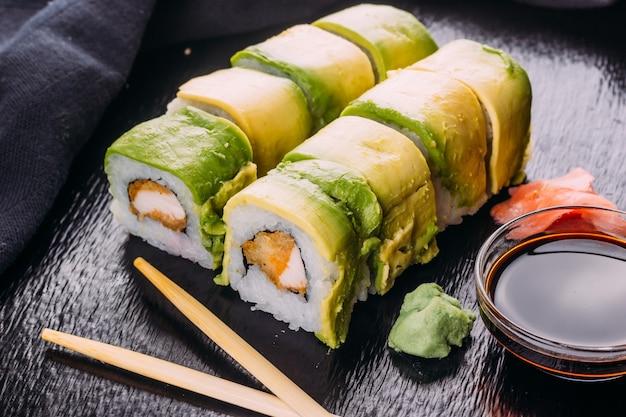 アボカドをまぶした巻き寿司にわさびと生姜を添えて