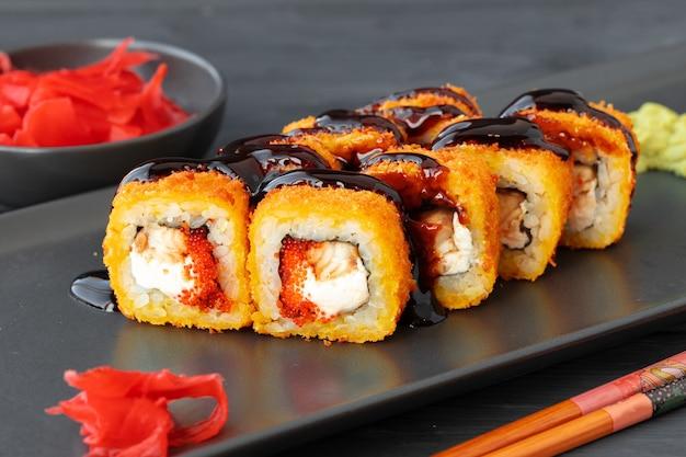 黒皿に天ぷらで揚げた巻き寿司をクローズアップ
