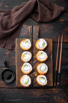 古い暗い木製のテーブルの上に、火で焼いたサーモン、シーバス、エビ、アボカドセットを添えた巻き寿司芸者