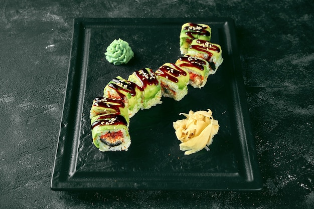 Суши-ролл зеленый дракон с авокадо, угрем и икрой тобико на черной тарелке на темном фоне. доставка еды. японская кухня
