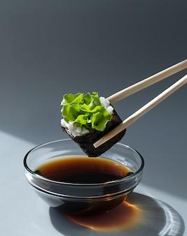 Суши-ролл держится палочками и обмакивается в соевый соус.
