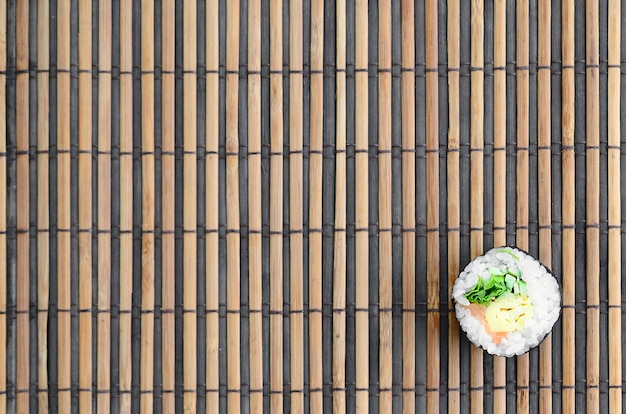 Sushi roll lie on a bamboo straw serwing mat background