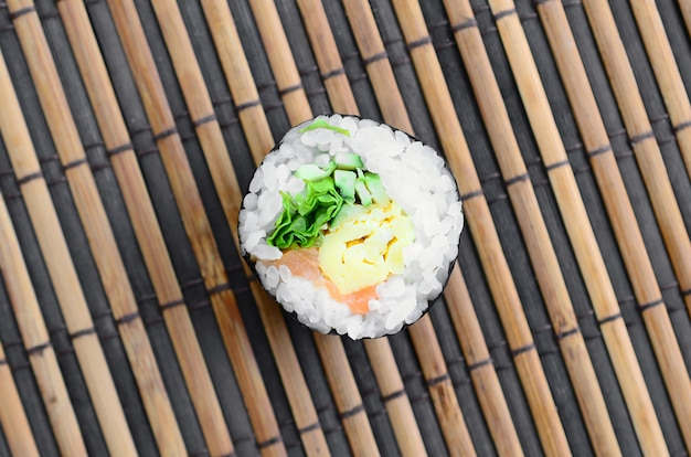 Sushi roll lie on a bamboo straw serwing mat