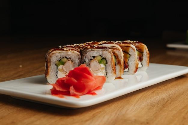 Суши-ролл (магуро) с креветками, копченым угрем, авокадо, сыром филадельфия на белой тарелке. суши-меню. японская еда.