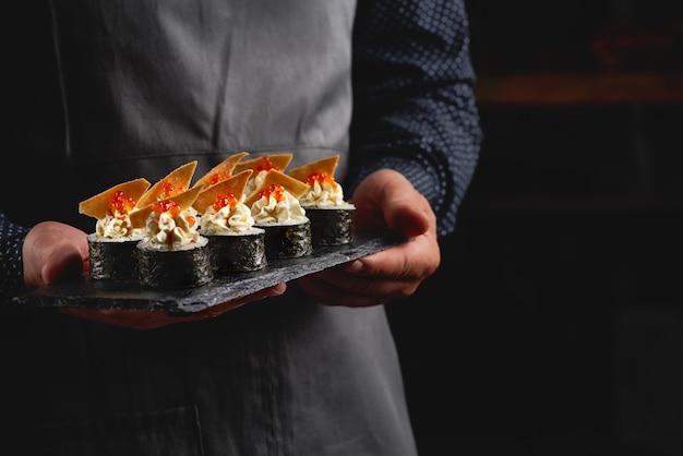 Суши ролл маки футо японская еда на черной каменной тарелке в руках официанта.