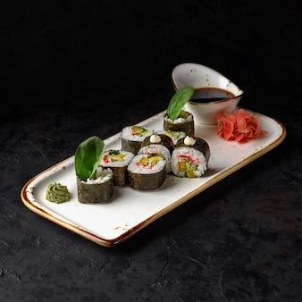 검은 돌 접시에 스시 롤 마키 후토 일본 음식. 스시 메뉴. 일본 음식.