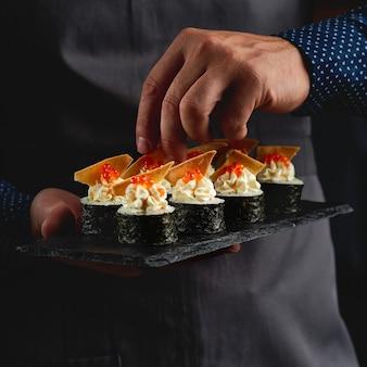 초밥, 노리, 아보카도, 연어 필렛, 치즈, 나초, 검은 돌 접시에 빨간 캐비어를위한 쌀과 함께 스시 롤 마키 후토 일본 음식.