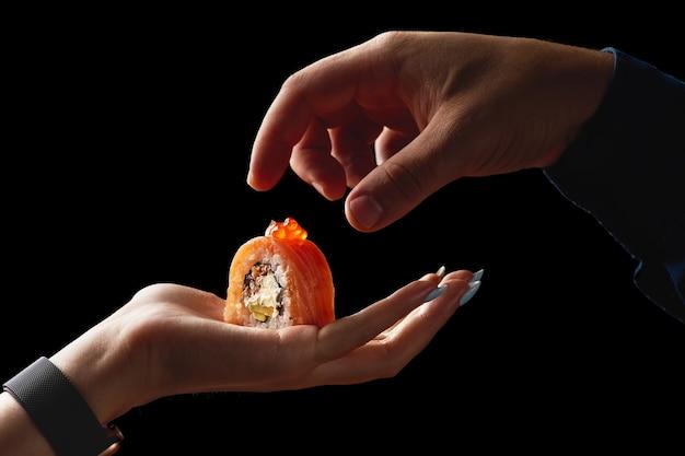 黒い表面の食品の概念の女性の手のひらに巻き寿司