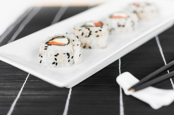 Sushi roll on white tray with chopsticks
