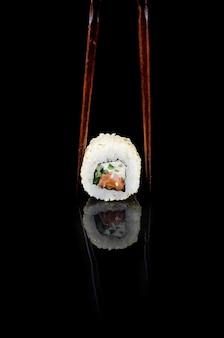 Суши-ролл филадельфия в кунжуте с лососем на черном фоне