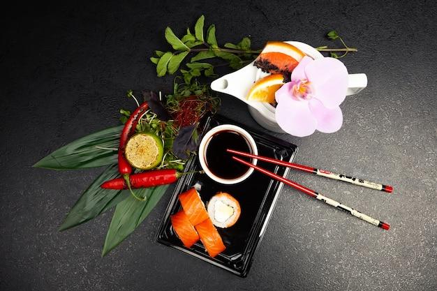 Суши-ролл филадельфия с авокадо, украшенный зеленью на тарелке, классические японские суши. традиционная японская еда с маки.