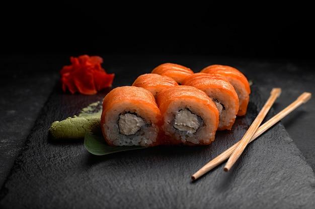 Суши-ролл филадельфия, с лососем и сливочным сыром, на черном сланце, на черном фоне