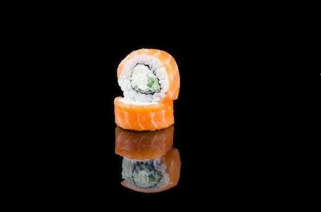 Суши-ролл филадельфия с лососем на черном фоне