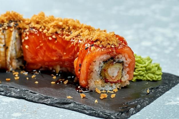 Суши-ролл филадельфия с лососем, креветками и угрем на черной тарелке на светлом фоне
