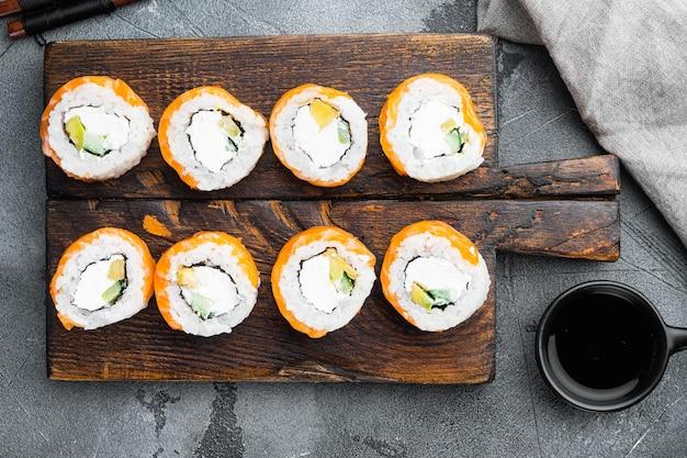 Суши-ролл ряд лосося и тунца с набором палочек для еды, на сером камне