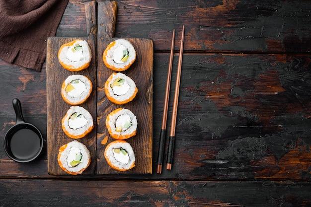 古い暗い木製のテーブルの上に、箸をセットした鮭とマグロの巻き寿司
