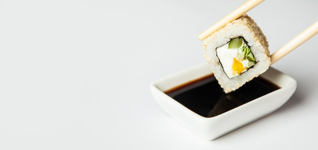 Sushi roll in sesame seeds is held with chopsticks and dipped in soy sauce soaked in soy sauce