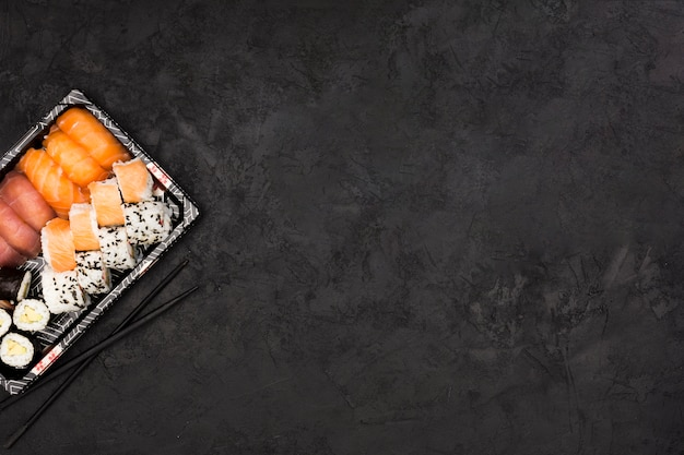 Sushi roll set on tray and chopsticks over dark textured surface with space for text