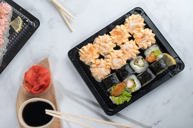 Sushi roll set with yellow cream sauce and shrimp in take away boxes