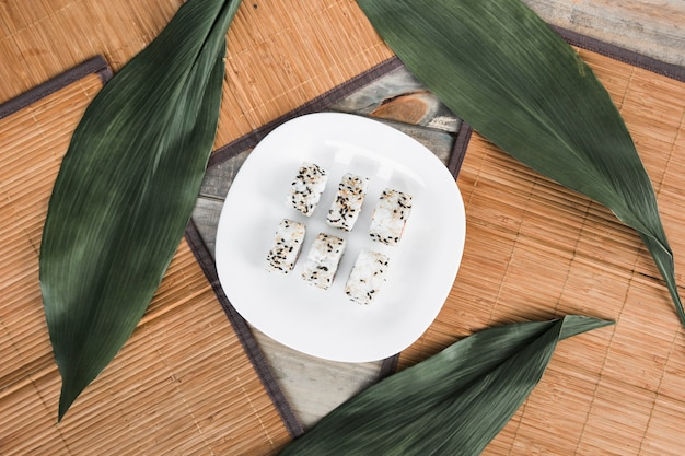 Sushi roll on white plate with green leaves and placemat