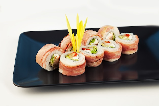 Sushi roll with bacon and fried sea bass on a black plate