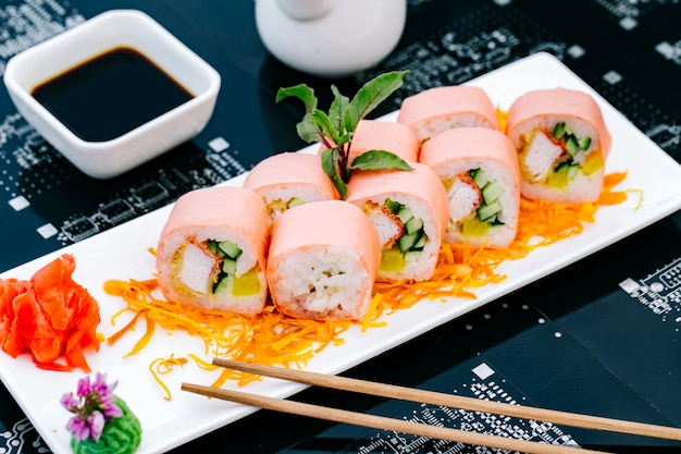 Sushi roll with crab sticks cucumber and bell pepper served with soy sauce ginger and tempura