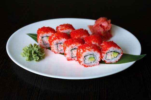 Суши ролл с красной икрой летучей рыбы, авокадо и сливочным сыром, на белой тарелке, на черной поверхности