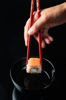 Суши-ролл с отражением на черном фоне. ресторан японской кухни. женские руки, держащие суши-роллы