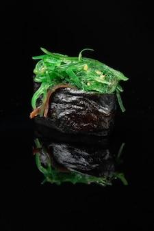 Суши-ролл с отражением на черном фоне с зелеными водорослями чука. ресторан японской кухни.