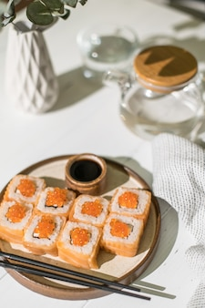 サーモンとキャビアの巻き寿司。日本食。白い木製の背景にサーモンとキャビアのロールパン