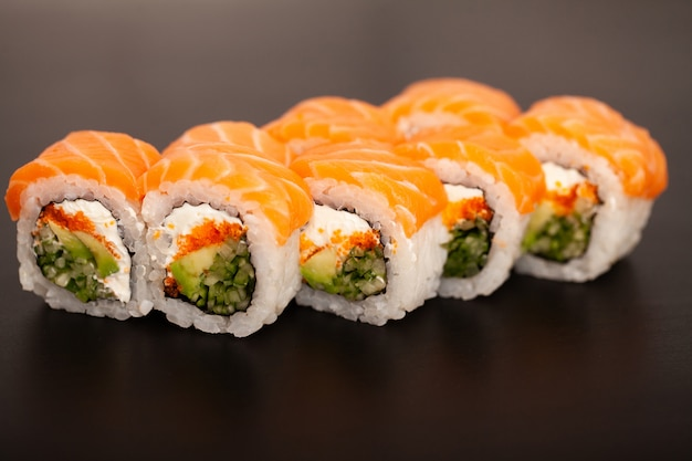 Sushi roll with salmon, cheese and avocado.