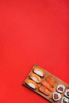 Sushi roll with salmon on chopping board against red background
