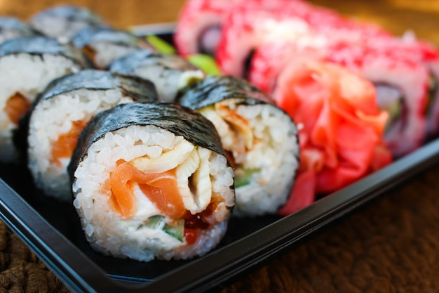 Sushi roll with salmon, cucumber, cheese, and caviar fish