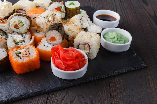 Sushi roll with salmon, eel, tuna, avocado, cream cheese philadelphia, caviar tobica, chuka. sushi menu. japanese food on table