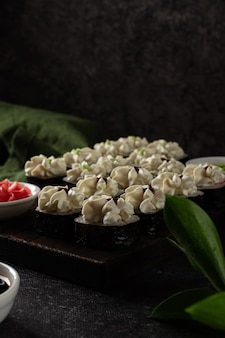 Sushi roll with salmon, smoked eel, avocado, cream cheese on a black background