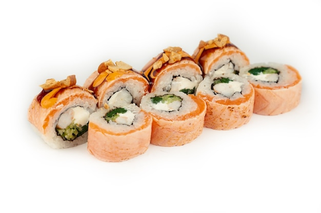Sushi roll with salmon tataki and blanched spinach on white plate