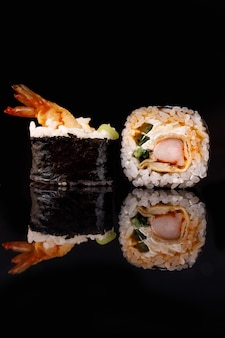 Sushi roll with shrimp on a black surface with reflection.
