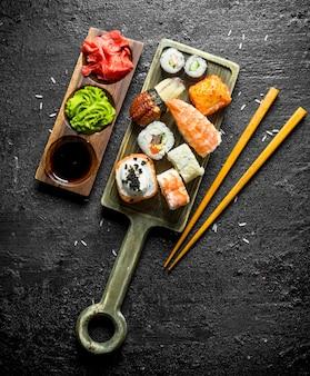 Суши, роллы и маки на разделочной доске с палочками и соусами. на черном деревенском фоне
